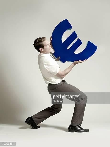 Businessman lifting large Euro symbol