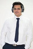 Portrait of handsome businessman listening music on wireless hedphones