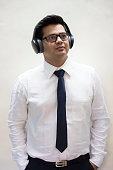 Thoughtful businessman listening music on wireless headphones