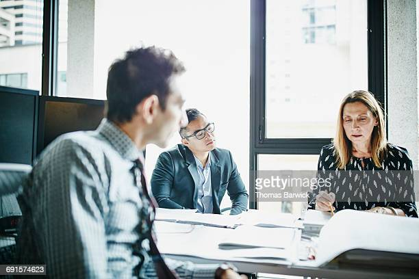 Businessman listening to colleague present ideas