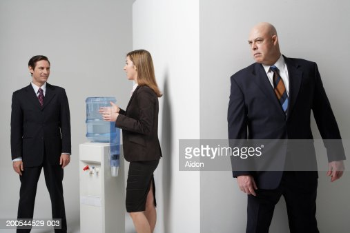 Businessman listening to colleagues conversation, studio shot : Stock Photo