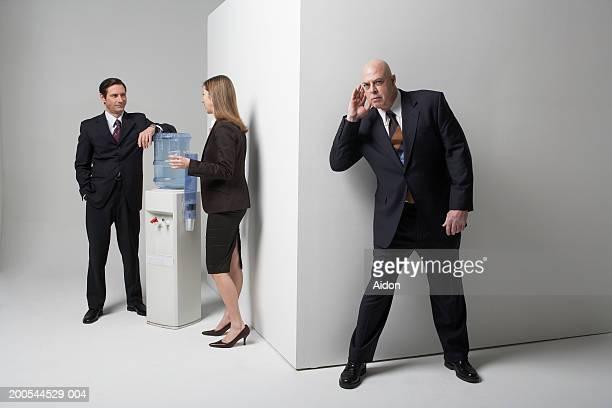 Businessman listening to colleagues conversation, studio shot