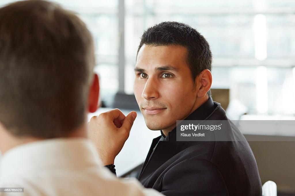 Businessman listening to coworker at meeting : Stock Photo