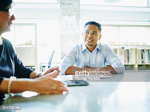 Businessman listening to coworker lead meeting