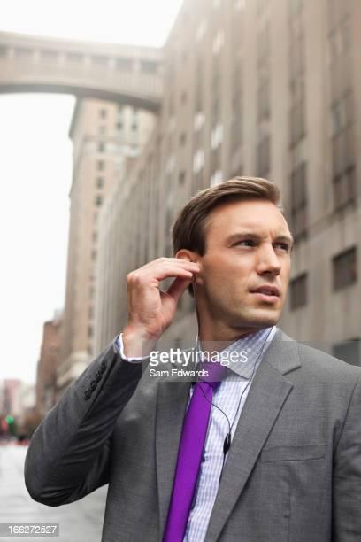 Businessman listening to earphones on city street