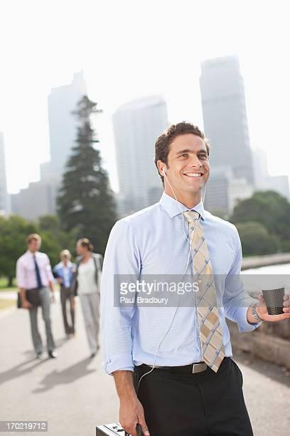 ビジネスマンに耳を傾けるのヘッドフォンと運ぶコーヒー