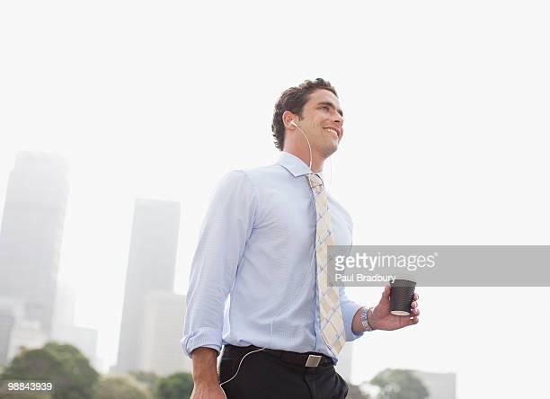 Geschäftsmann, tragen Kopfhörer hören und Kaffee