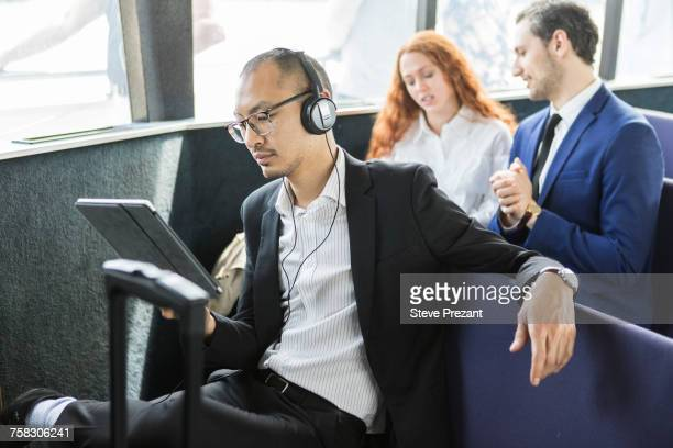 Businessman listening to headphones looking at digital tablet on passenger ferry