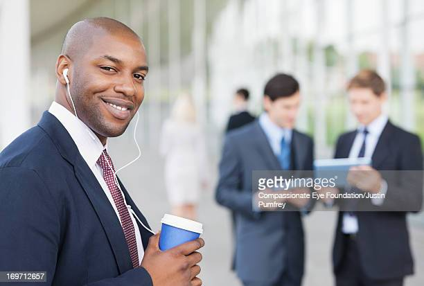 Businessman listening to headphones outdoors