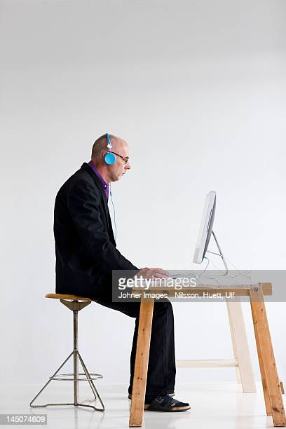 Businessman listening to headphones, using computer at desk
