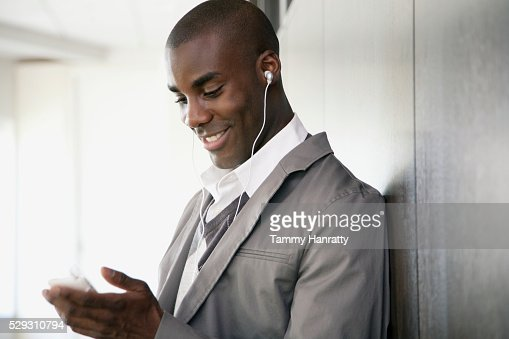 Businessman listening to MP3 player : Stockfoto