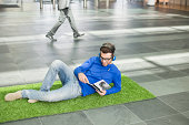 Businessman listening to music and reading book while relaxing on grass mat in an office lobby