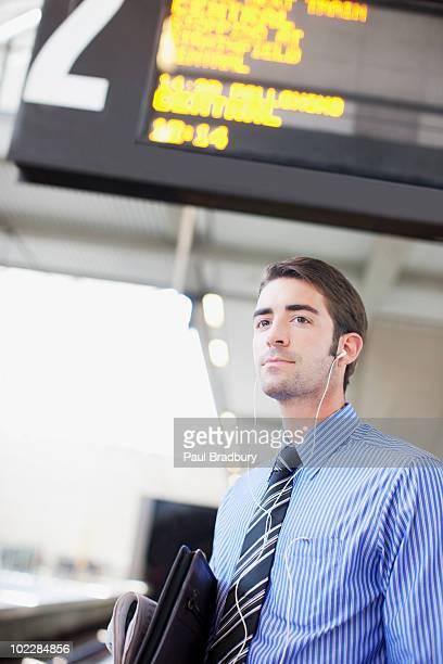 Geschäftsmann, hören Musik und warten auf Zug