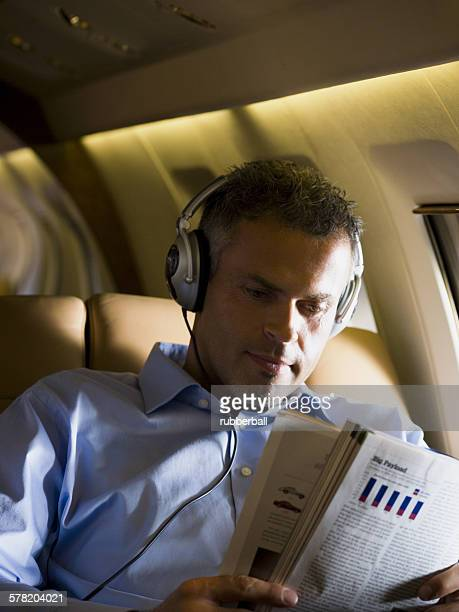 A businessman listening to music on headphones and reading a magazine in an airplane