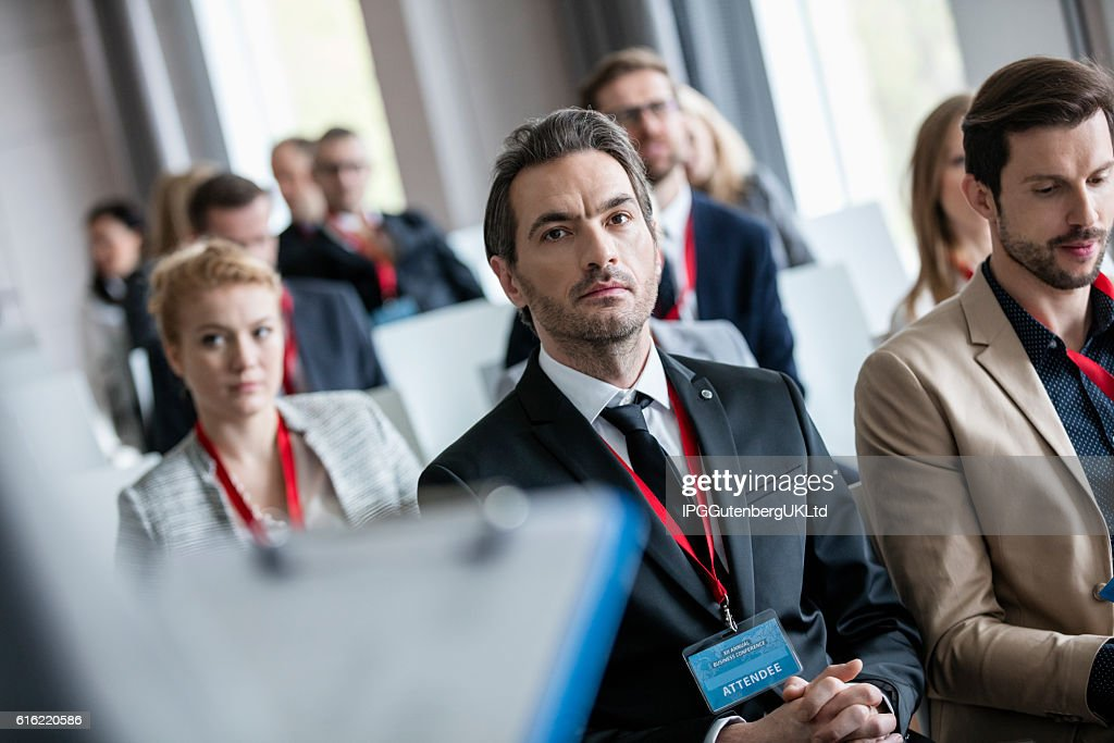 Businessman listening to presentation during seminar : Stock Photo