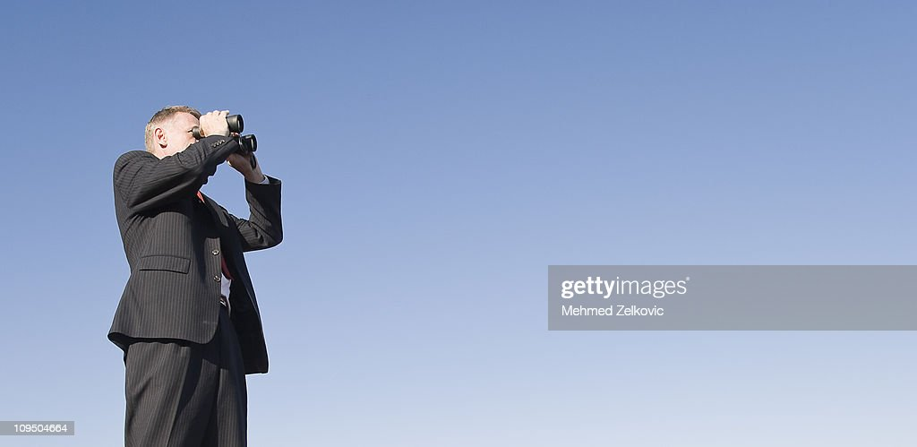Businessman looking ahead with binoculars : Stock Photo