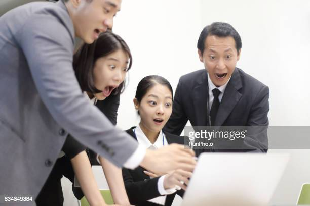 businessman looking at a computer and looking surprised
