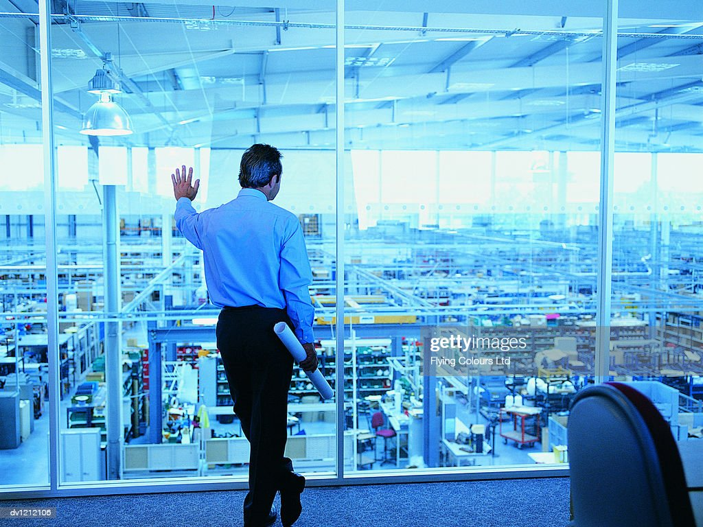Businessman Looking at a Factory From His Office