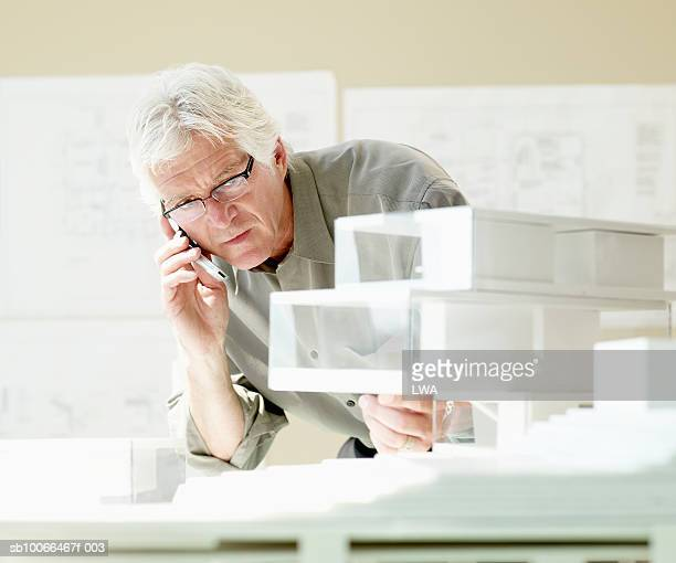 Businessman looking at architectural model, using mobile phone