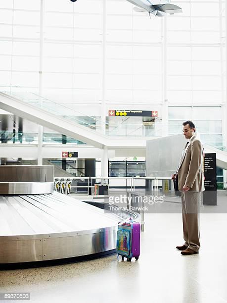 Businessman looking at bag at baggage claim