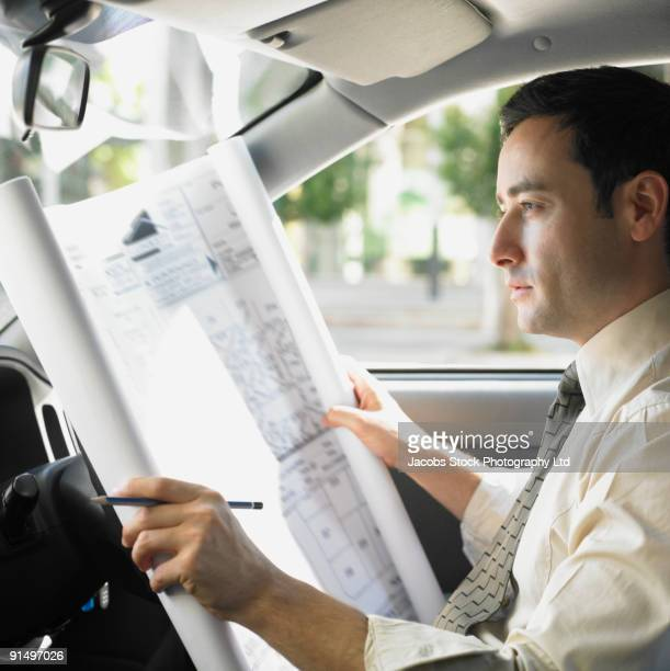 Businessman looking at blueprints in car
