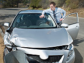 Businessman looking at car accident damage
