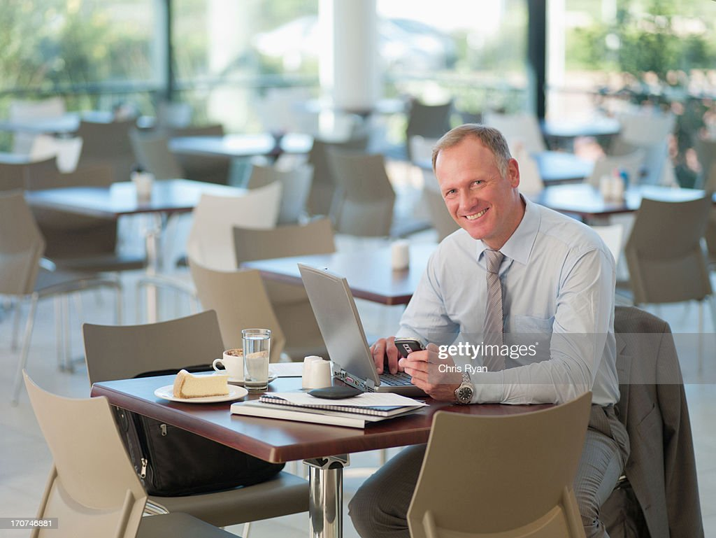 Businessman looking at cell phone in cafeteria : Stock Photo