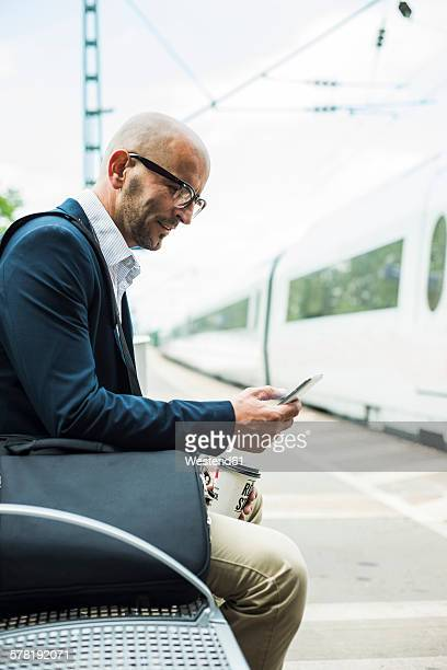 Businessman looking at cell phone on railway platform