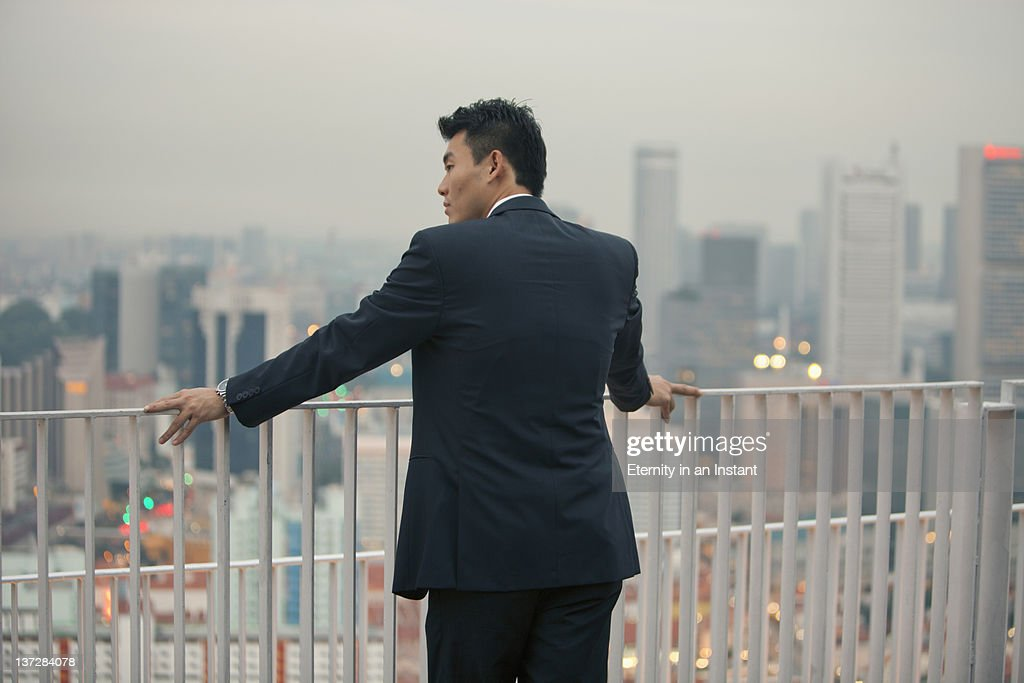 Businessman looking at city at dusk : Stock Photo