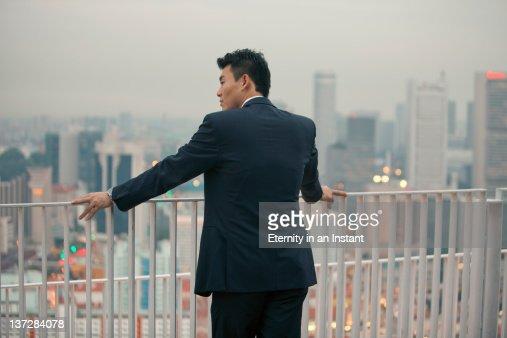 Businessman looking at city at dusk : Foto de stock