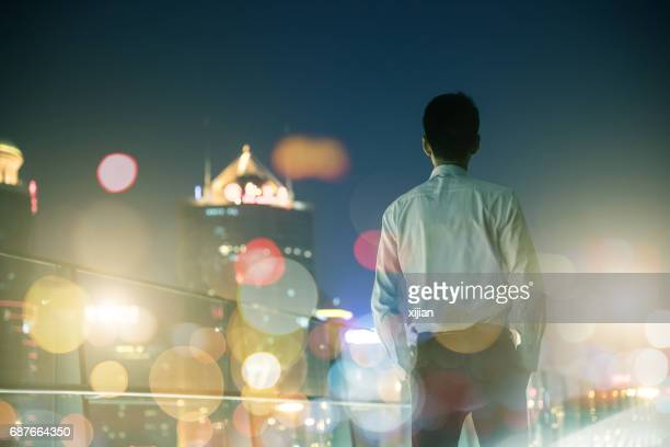 Businessman looking at city at night
