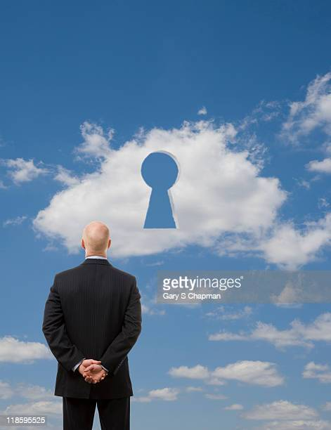 Businessman looking at cloud with keyhole