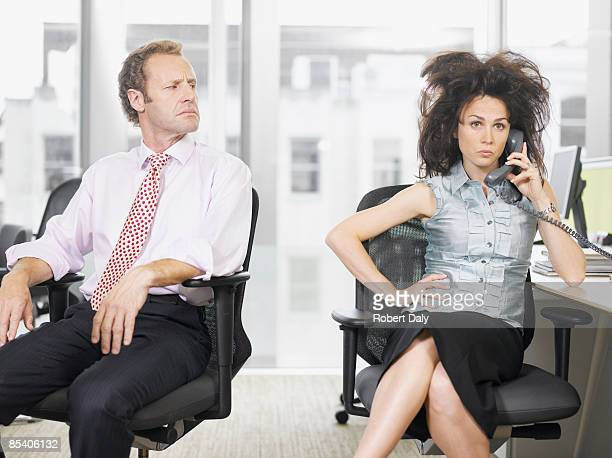 Businessman looking at co-worker talking on telephone