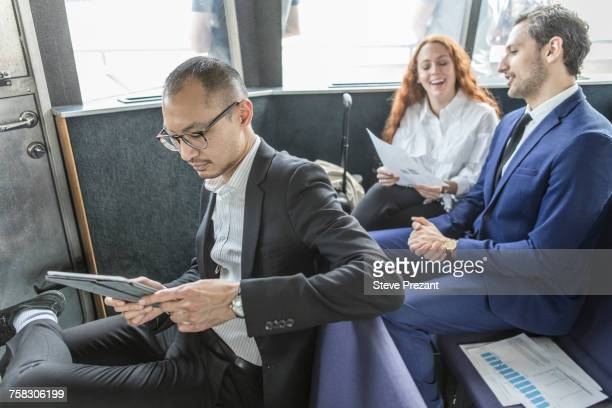 Businessman looking at digital tablet on passenger ferry