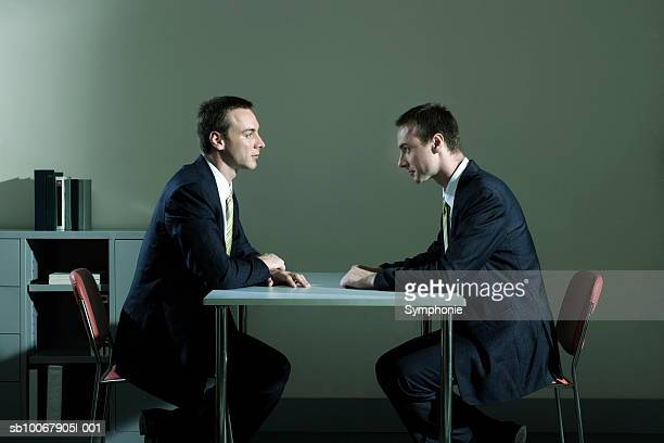 Businessman looking at duplicate sitting at table in office (Digital Composite)