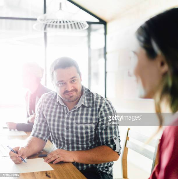 Businessman looking at female colleague in meeting