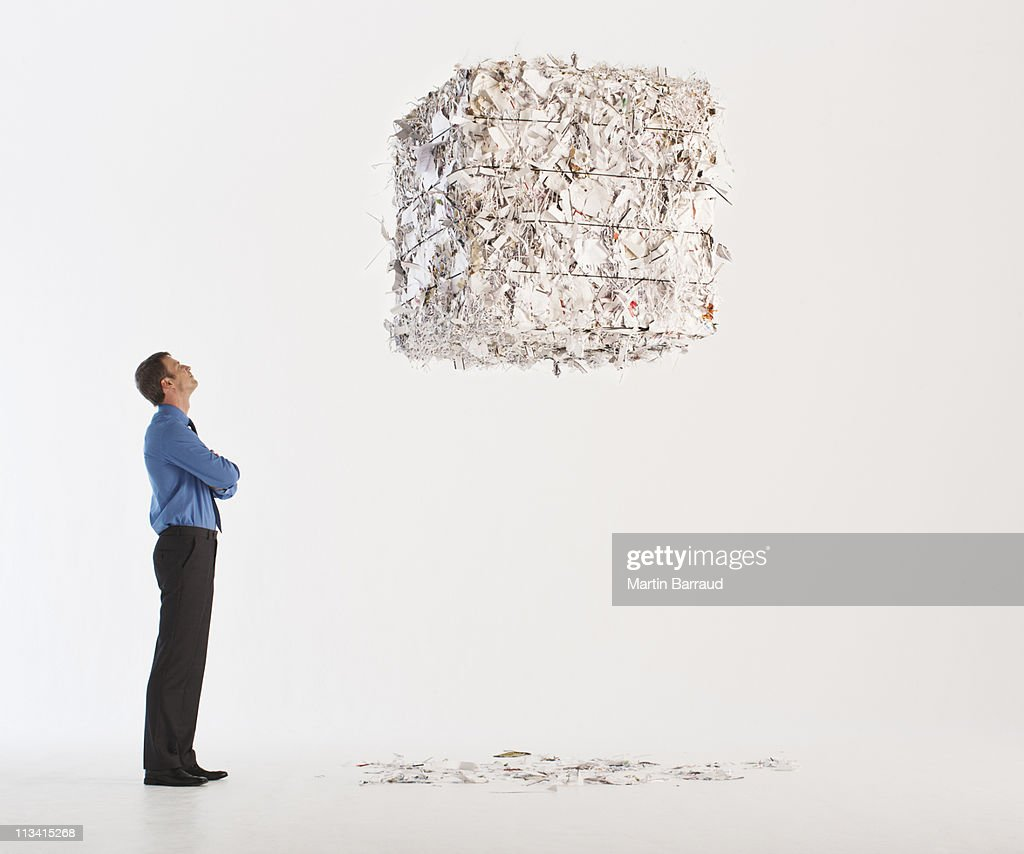 Businessman looking at floating paper bale : Stock Photo