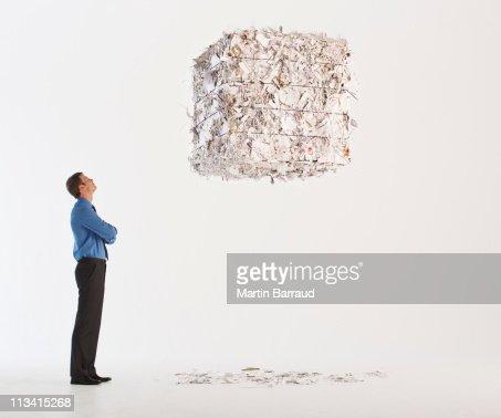 Businessman looking at floating paper bale : Bildbanksbilder