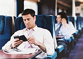 Businessman Looking at His PDA on a Passenger Train