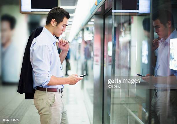 Businessman looking at his phone and waiting for the subway in Beijing
