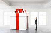Businessman looking at huge present box in white brick interior. 3D Rendering