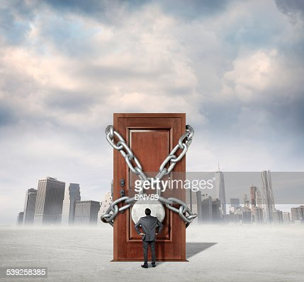 Businessman looking at locked door with city skyline in background