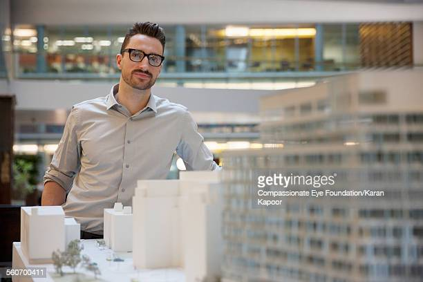 Businessman looking at model building