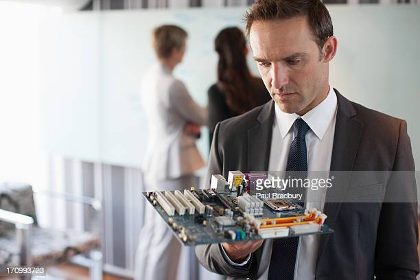 Businessman looking at motherboard in office