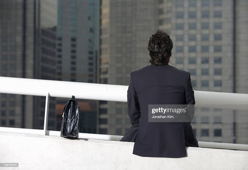 Businessman looking at office building, rear view : Stock Photo