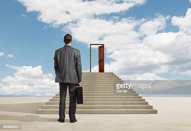 Businessman looking at opportunity created by an open door