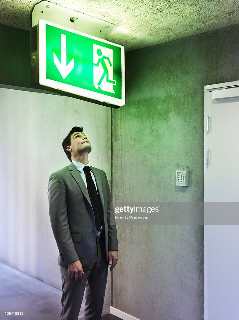 Businessman looking at oversized exit sign : Stock Photo