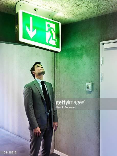 Businessman looking at oversized exit sign