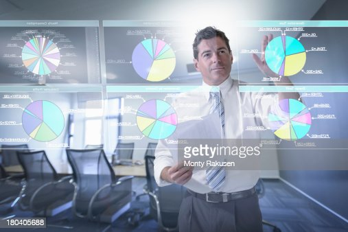 Businessman looking at pie charts on interactive screen