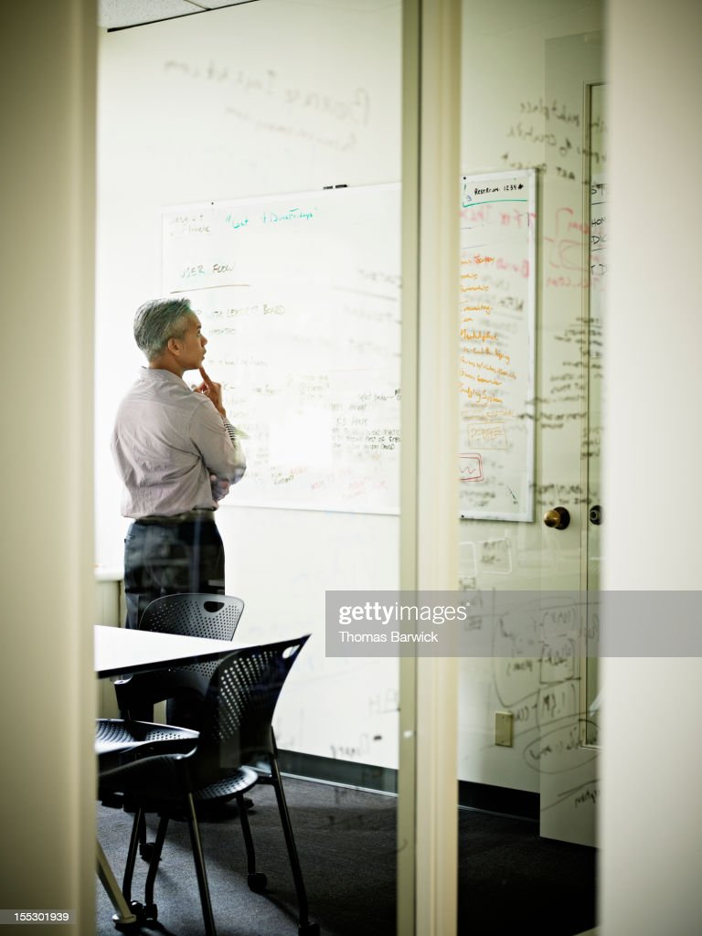 Businessman looking at project on white board : Stock Photo